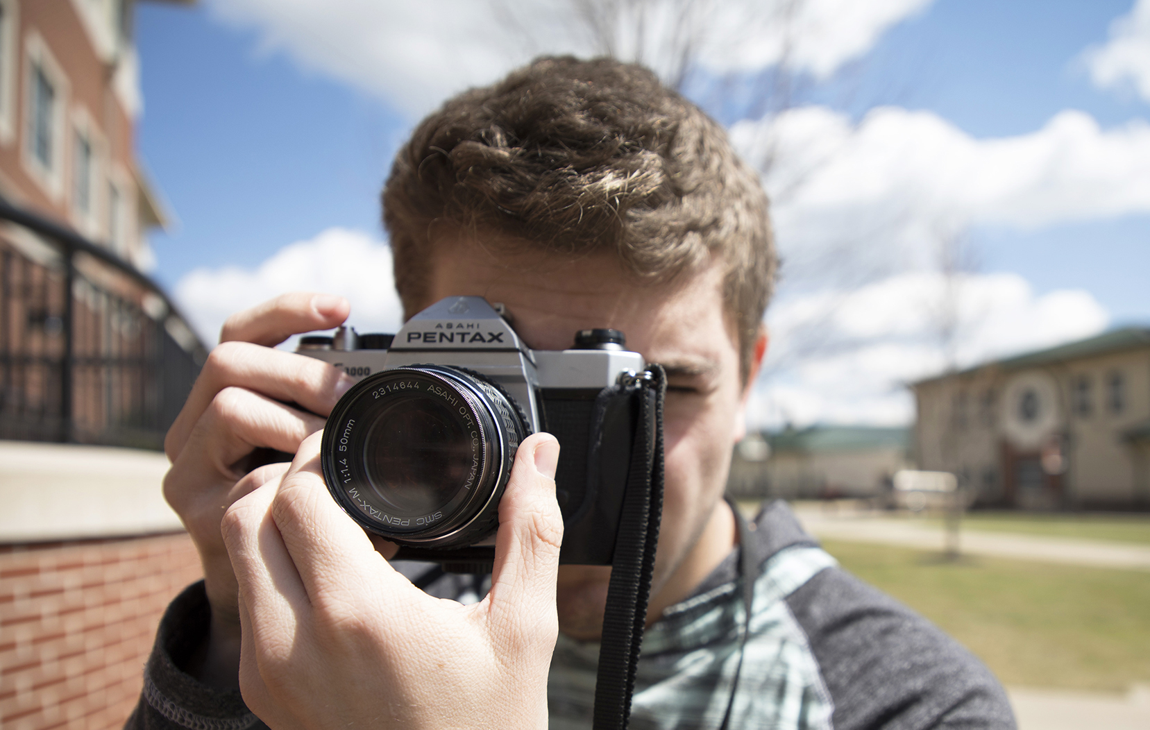 Male student looking through a camera
