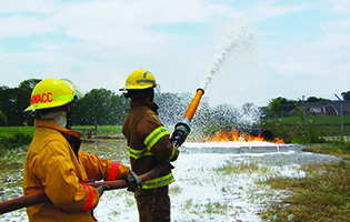 Two Fire Science students holding a hose pointed towards a fire