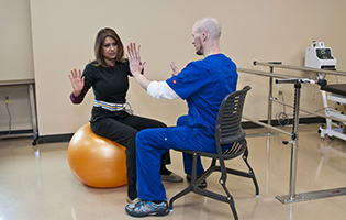 Male physical therapy assistant student practicing in class