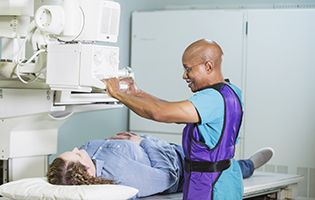 Older bald black man setting up a machine to x-ray a white woman with brown hair laying on a table